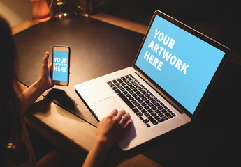 User with Laptop and Smartphone in Dark Room Mockup 2