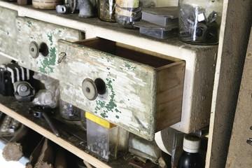 Vintage old wooden drawer in cupboard in workshop. half open.