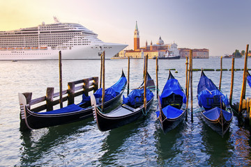 Venice with gondolas on Grand Canal against San Giorgio Maggiore church in Italy with large cruise ship in beautiful summer morning sunrise light