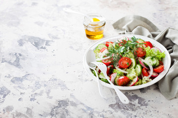 Fresh salad with cherry tomatoes, cucumbers, radishes, dill and olive oil, selective focus