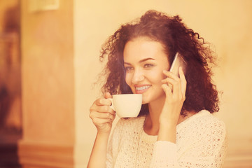Attractive woman savouring coffee and speaking by cellphone in cafe