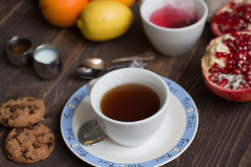 Fruit tea with lemon, milk,honey,orange, pomegranate, on a woode