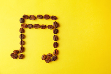 Musical note made of coffee beans on yellow background