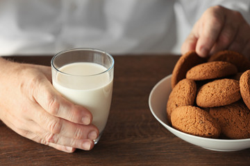 Senior man holding glass of milk and cookie
