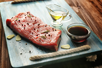 Delicious steak smearing with aromatic garlic and pepper on wooden board