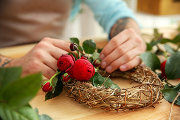 Close up view of tattooed florist preparing flower composition at workplace
