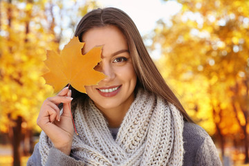 Portrait of beautiful young woman in autumn park on sunny day, close up