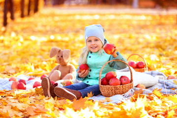 Cute little girl with basket full of red apples in autumn park