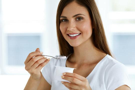 Beautiful Woman Eating Organic Yogurt. Healthy Diet Nutrition