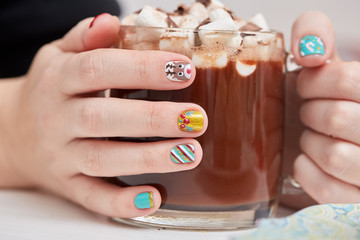 Mug with cocoa and marshmallows in female hands.