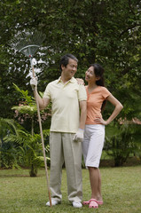 Couple standing side by side in garden, looking at each other, man holding garden rake