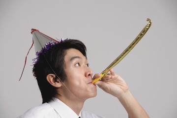 Man wearing party hat and using noisemaker