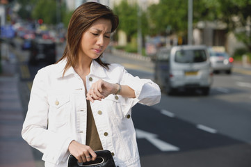Woman standing by road, looking at watch