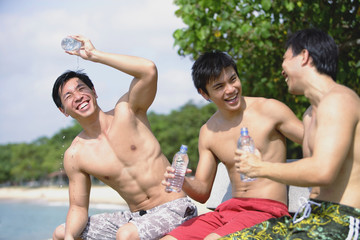 Three men sitting side by side, holding bottle of water