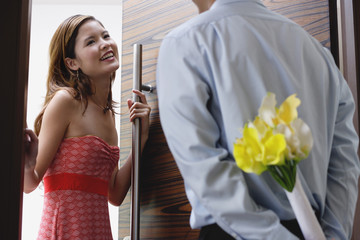 Woman opening door, man with flowers behind his back