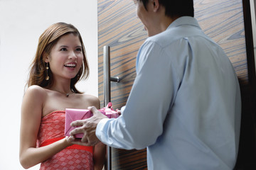 Couple standing at doorway, man giving woman a present