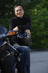 Man leaning on motorcycle, holding helmet, smiling at camera