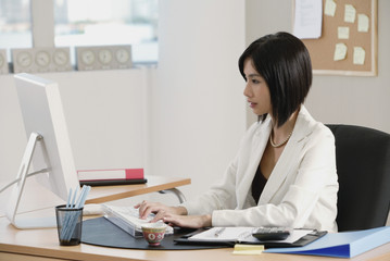 A woman sits at her desk and works