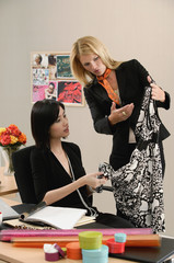 Two female colleagues look at a dress while at work