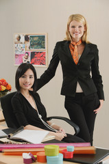 Two female colleagues smile at the camera together