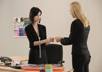 One woman gives another her business card