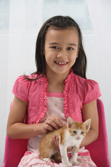 Young girl with kitten on her lap