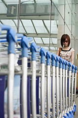 Young woman retrieving trolley at the airport