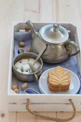 Breakfast in a white wooden crate, A pewter teapot, sugar cubes and a maple leaf shaped cookie.