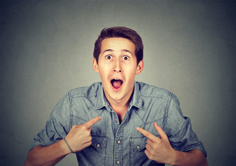 young happy surprised man pointing at himself you mean me