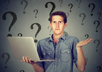 Perplexed young man with laptop many questions and no answer