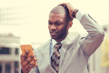 stressed man holding cellphone looking at screen with cross face expression