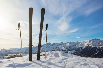Skis in mountains against blue sky