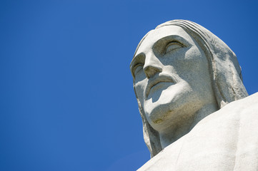 Close-up portrait of the face of Christ the Redeemer at Corcovado against blue sky in Rio de Janeiro Brazil