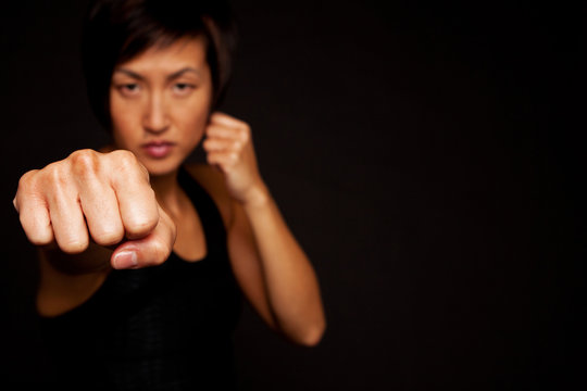 Fit Asian woman doing martial arts and working out.