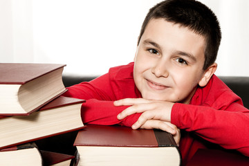 happy schoolboy lying on books