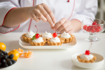 Close up of female professional confectioner hands topping custard tarts with sweet cherry fruits
