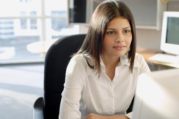 Female executive facing computer, portrait