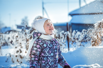 child playing in the snow drifts of