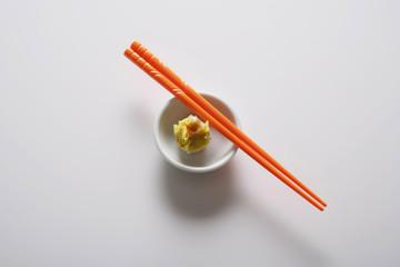 dim sum in bowl with orange chopsticks