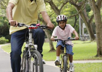 A father and son ride their bikes together