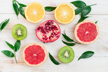 sliced fruit on wooden white background, top view