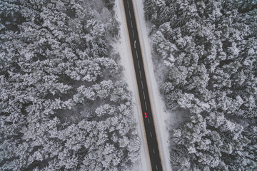 Snowy road with a car in the forest