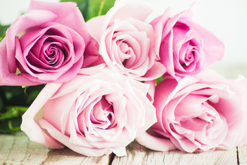 Blurred pink roses on wooden background