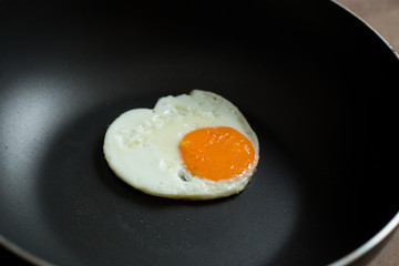 Fried egg on pan and fresh eggs.