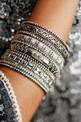 Close-up of woman's arm with silver bangles