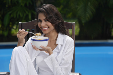 Woman in chair by the pool, holding bowl of cereal and looking at camera