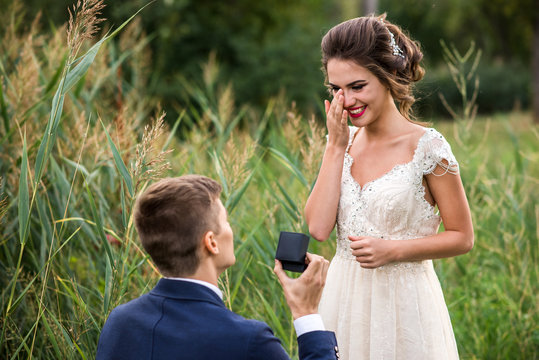 Young man makes a proposal to get married, the bride is crying from happiness
