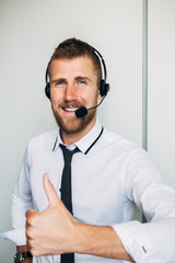 Portrait of handsome young male operator in headset looking at camera and smiling while standing against white background