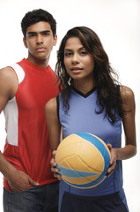 Young couple with beach ball looking at camera