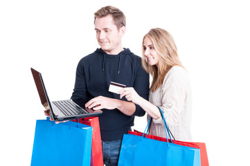 Couple holding shopping bags and paying online